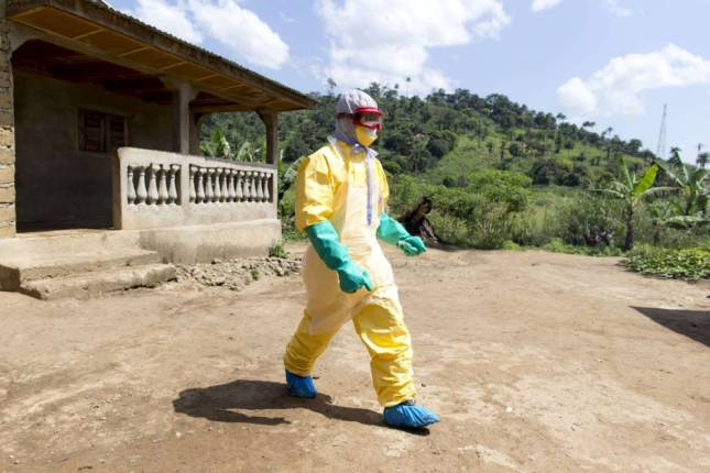 An health worker from Guinea's Red Cross wearing a Personal Protective Equipments (PPE) leaves the house of a victim of the Ebola virus in Patrice disitrict in Macenta, in Guinea on November 21, 2014.  The deadliest Ebola epidemic on record has killed more than 5,000 people in west Africa and infected almost three times that number, according to the World Health Organization. The virus emerged in Guinea at the start of the year and has infected around 1,900 Guineans, killing almost 1,200. AFP PHOTO KENZO TRIBOUILLARDKENZO TRIBOUILLARD/AFP/Getty Images