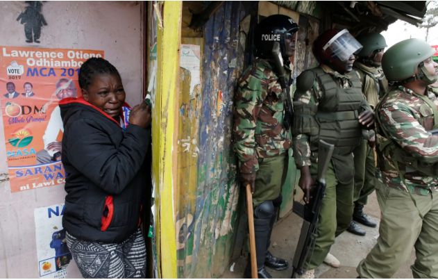 woman cries behind policemen during post August poll clashes.